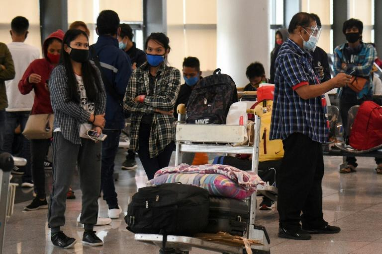 The reimposition of a coronavirus lockdown in Manila has left many stranded at the Philippine capital's domestic airport (AFP Photo/Ted ALJIBE)