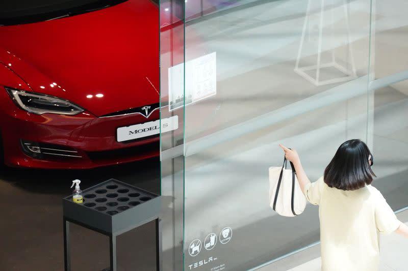 A woman walks past a Tesla dealership in Hanam