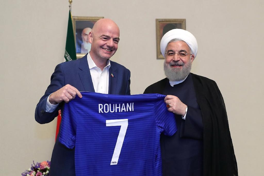Iranian President Hassan Rouhani (R) and FIFA president Gianni Infantino hold a football shirt with Rouhani's name during Infantino's visit to the capital Tehran on March 1, 2018