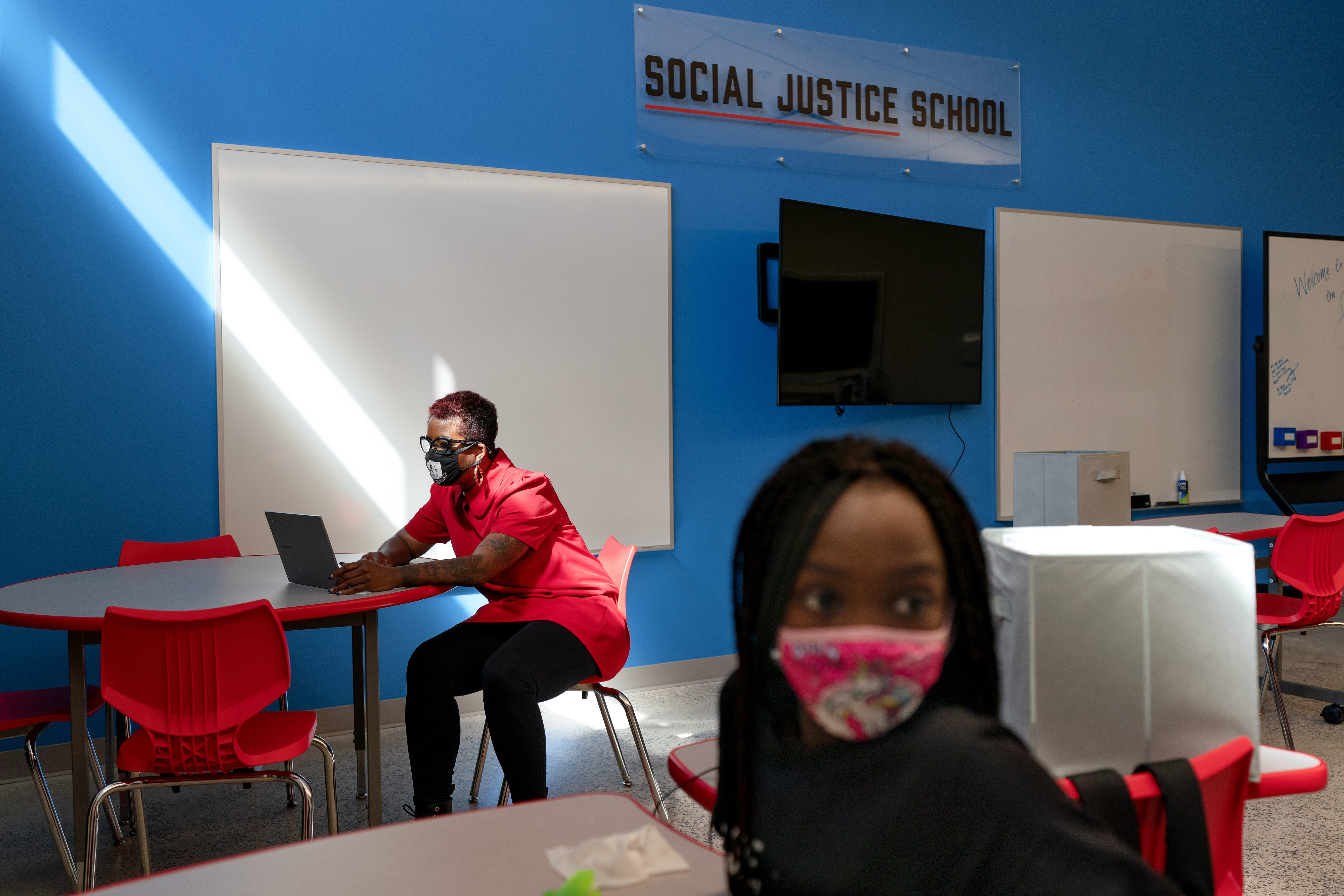 In this Tuesday, Sept. 29, 2020, photo a tech problem is solved by a teacher as a student attends her English Language Arts class at The Social Justice Public Charter School, in Washington. (AP Photo/Jacquelyn Martin)