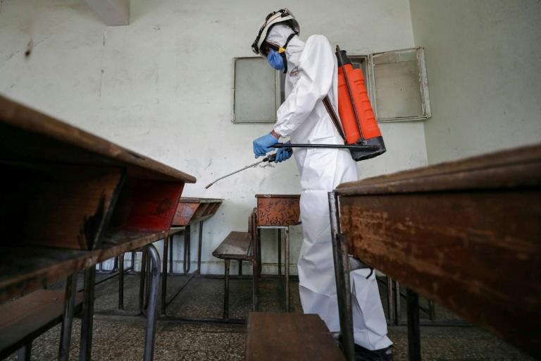 "A member of the Syrian Civil Defence, also known as the ""White Helmets"" disinfects a classroom at a school in Syria's rebel-held northwestern city of Idlib's displacement camps. (AFP Photo/OMAR HAJ KADOUR)"