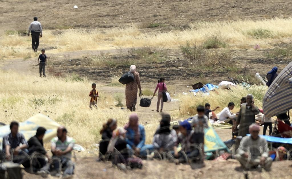 Syrian Kurds return to Kobane in Turkey's Sanliurfa province near the border with Syria after clashes in the city on June 27, 2015 (AFP Photo/Bulent Kilic)