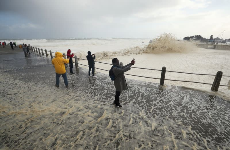 People watch huge swells as a cold front moves in over Cape Town, South Africa