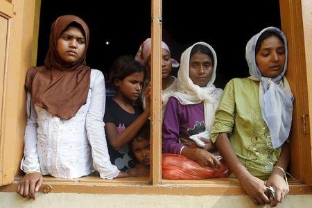 Migrants, believed to be Rohingya, look out the window of a shelter they are staying at since being rescued along with hundreds of others on Sunday from boats in Lhoksukon, Indonesia's Aceh Province May 12, 2015. REUTERS/Roni Bintang