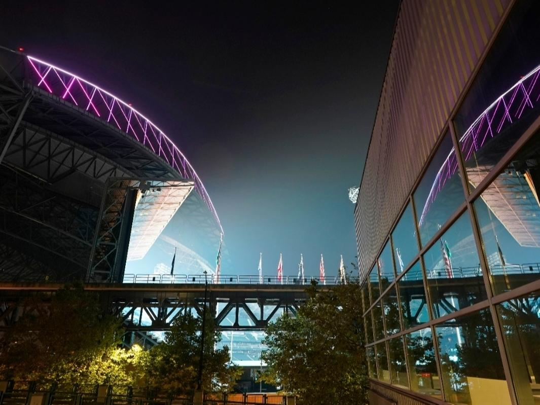 Smoke from wildfires is seen in the air as lights from T-Mobile Park, left, are reflected in a window of CenturyLink Field on Thursday, Sept. 10, 2020, in Seattle.