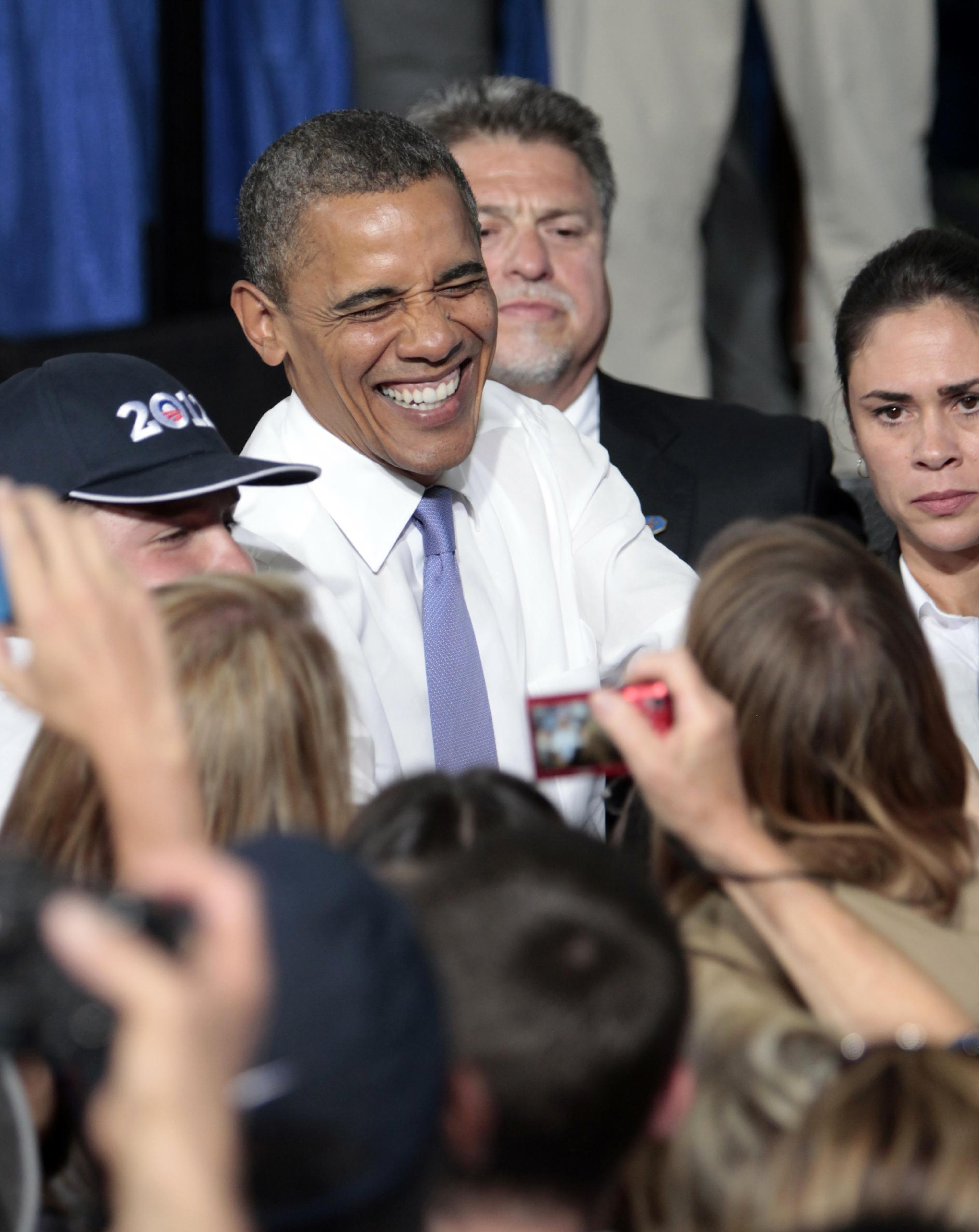 President Barack Obama laughs as he visits with supporters following his campaign stop at the Truckee Meadows Community College in Reno, Nev., Tuesday, Aug. 21, 2012. (AP Photo/Rich Pedroncelli)