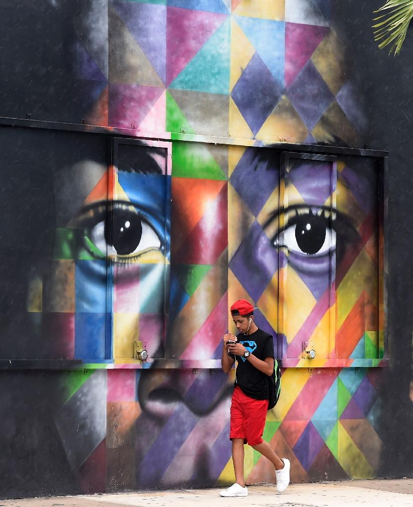 A man walks in front of a mural by Brazilian artist Kobra in the Wynwood neighborhood in Miami, Florida, on September 28, 2016 (AFP Photo/Rhona Wise)