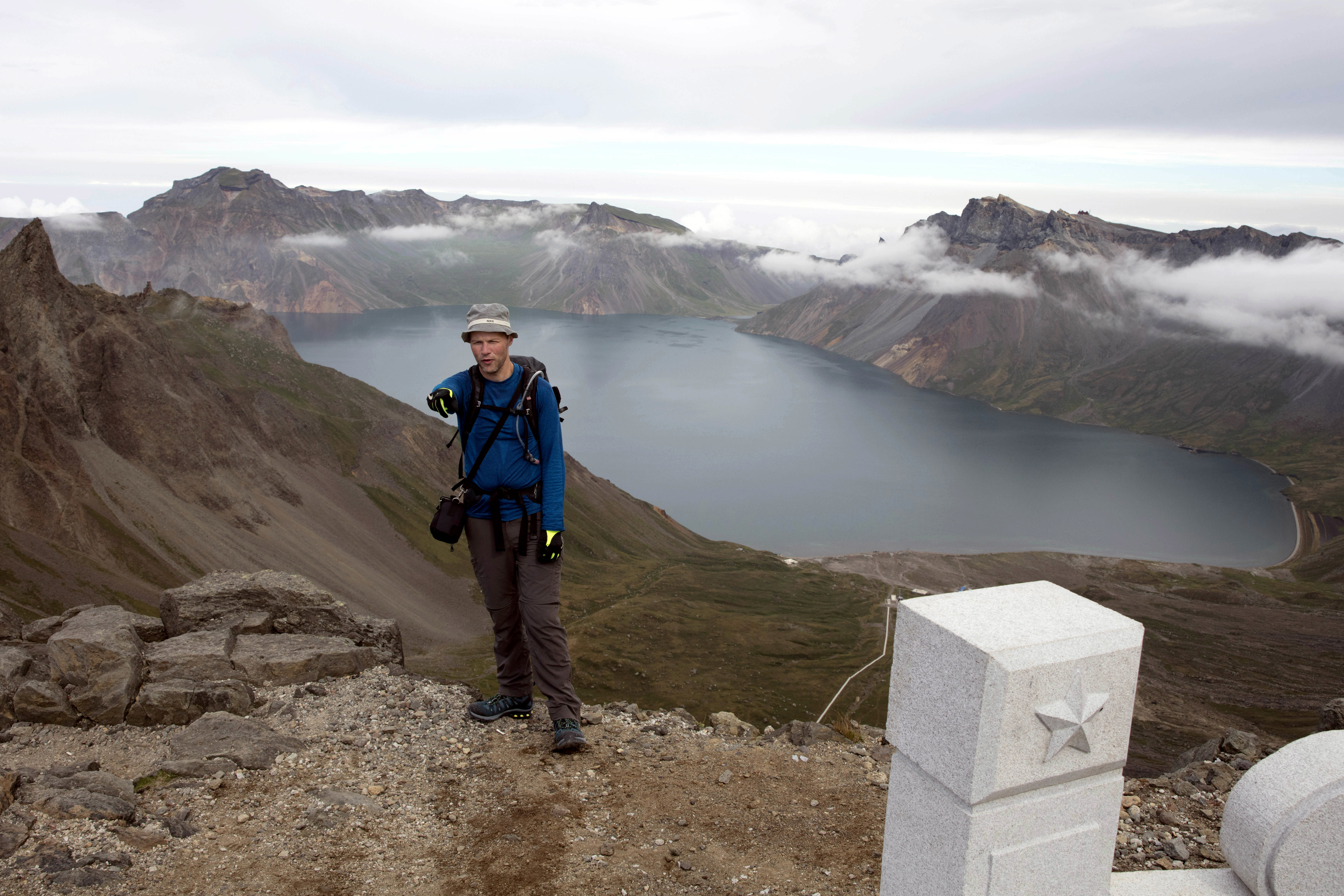 In this Saturday, Aug. 18,2018, photo, Tarjei Naess Skrede of Norway who is hiking with Roger Shepherd of Hike Korea stands near a view of the caldera and Lake Chon on Mount Paektu in North Korea. Hoping to open up a side of North Korea rarely seen by outsiders, Shepherd, a New Zealander who has extensive experience climbing the mountains of North and South Korea is leading the first group of foreign tourists allowed to trek off road and camp out under the stars on Mount Paektu, a huge volcano that straddles the border that separates China and North Korea. (AP Photo/Ng Han Guan)