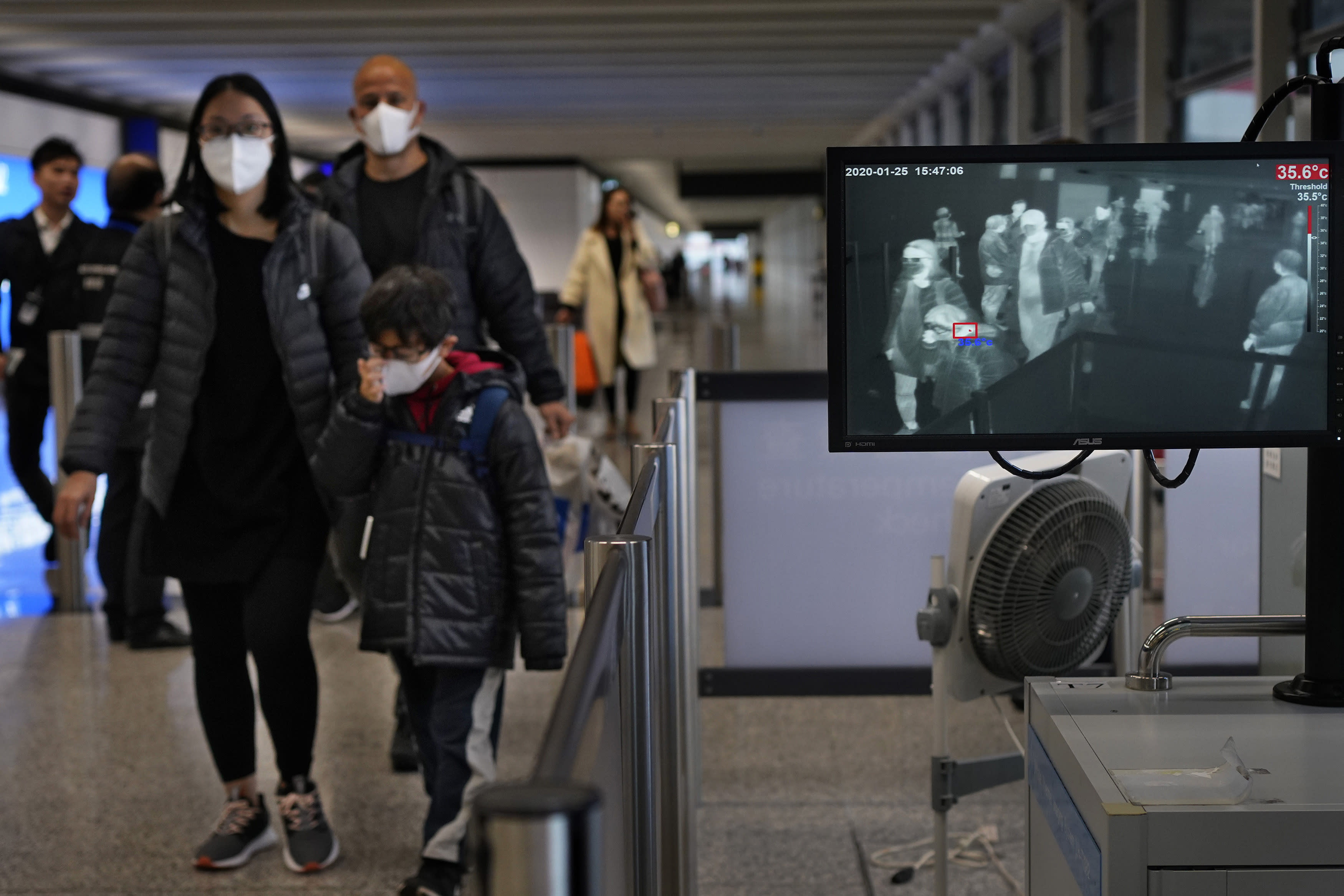 Health surveillance officer use temperature scanner to monitor passengers arriving at Hong Kong International Airport in Hong Kong Saturday, Jan. 25, 2020. Hong Kong has declared the outbreak of a new virus an emergency and will close primary and secondary schools for two more weeks after the Lunar New Year holiday. City leader Carrie Lam also announced Saturday that trains and flights from the city of Wuhan would be blocked. (AP Photo/Vincent Yu)