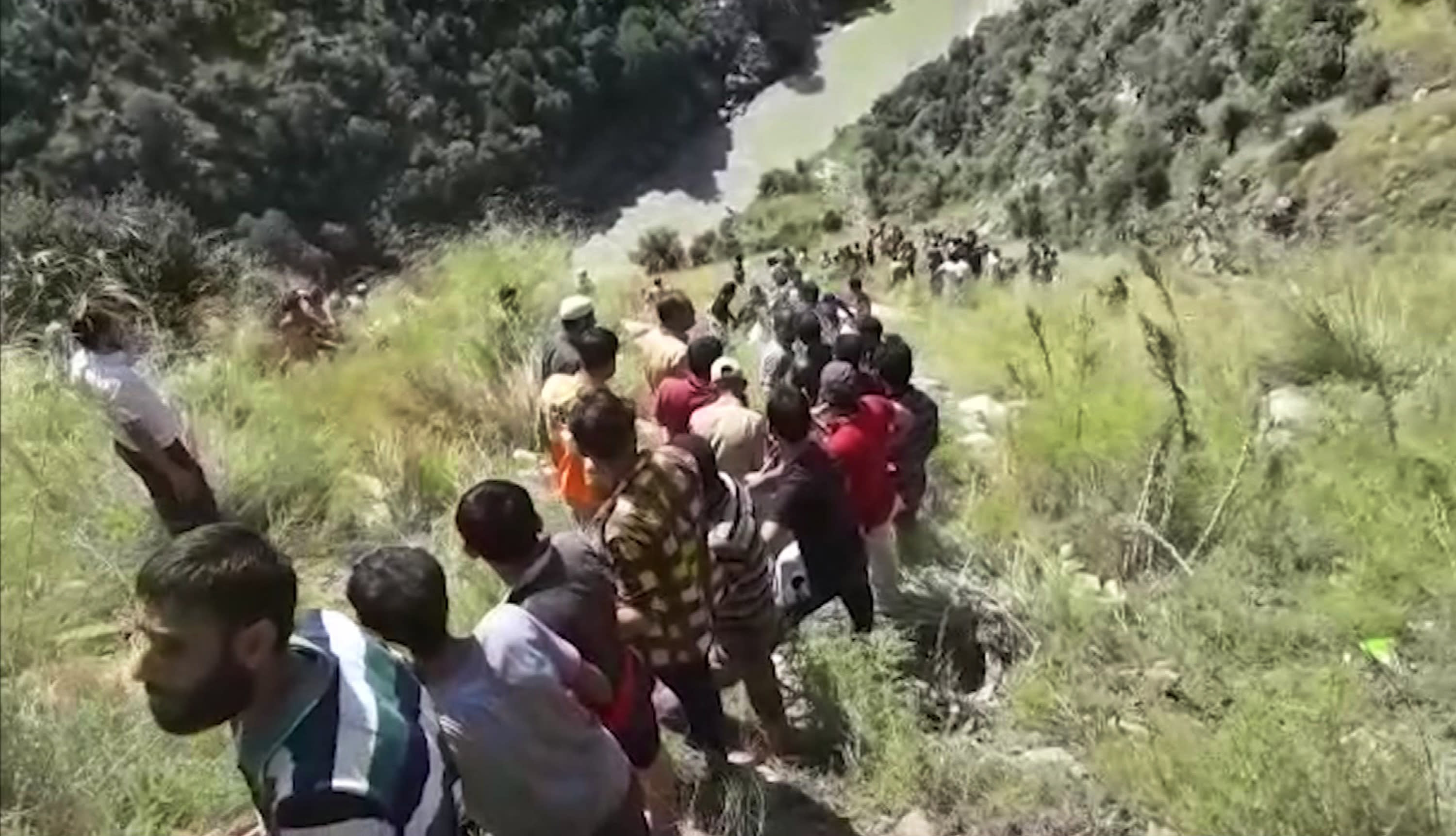 In this grab made from video provided by KK Productions, rescuers try to reach a bus that fell into a gorge in Kishtwar, about 217 kilometers (135 miles) southeast of Srinagar, Indian-controlled portion of Kashmir, Friday, Sept. 14, 2018. The bus fell off a road into a deep gorge killing more than a dozen people. (KK Productions via AP)