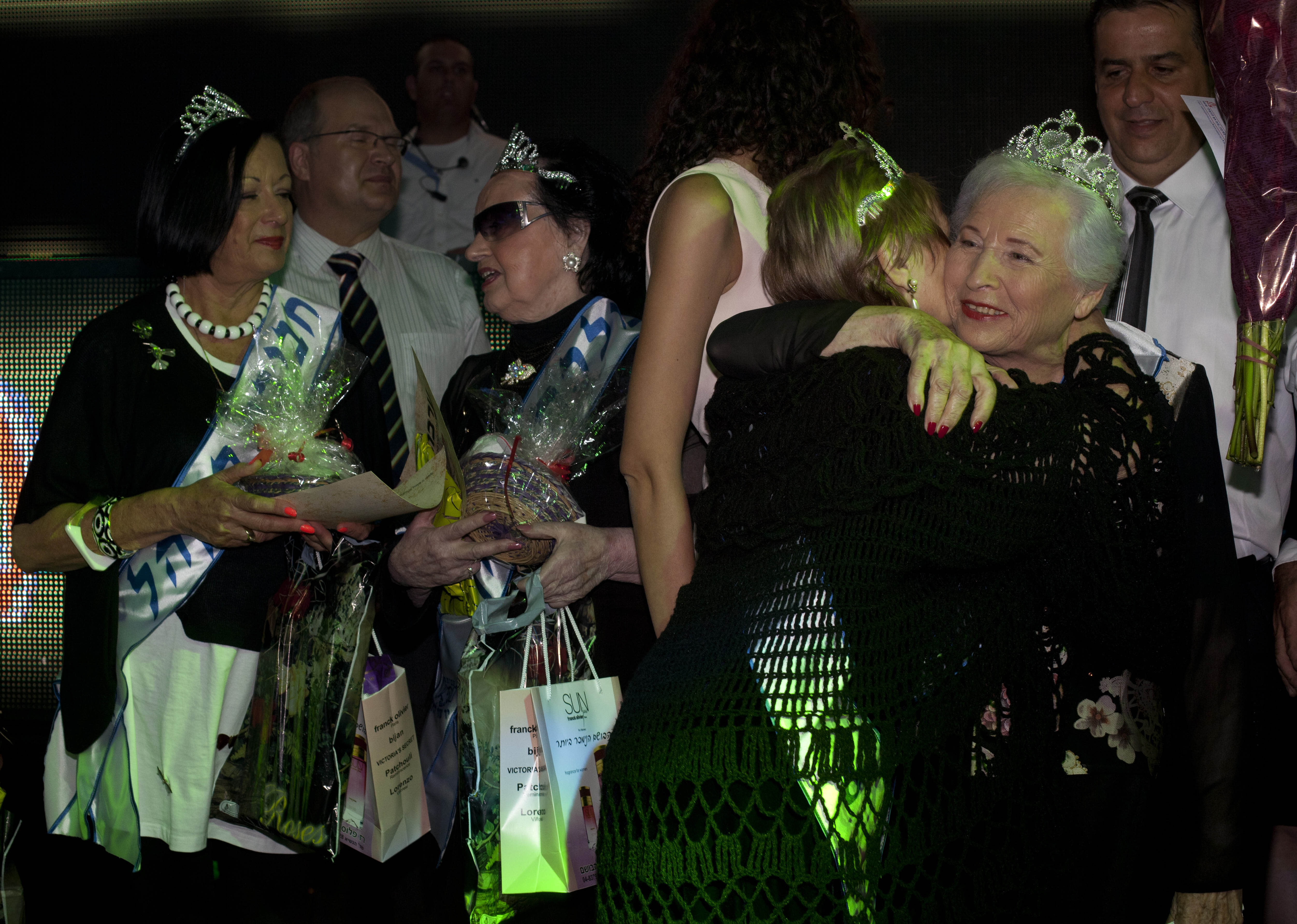 """Hava Hershkovitz, right, a Holocaust survivor and winner of a beauty pageant is congratulated by another participant, in the northern Israeli city of Haifa, Thursday, June 28, 2012. Fourteen women who lived through the horrors of World War II paraded on stage Thursday night in an unusual pageant, vying for the honor of being Israel's first """"Miss Holocaust Survivor."""" (AP Photo/Sebastian Scheiner)"""