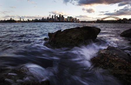 Small waves crash over rocks across the harbour from the Sydney city skyline