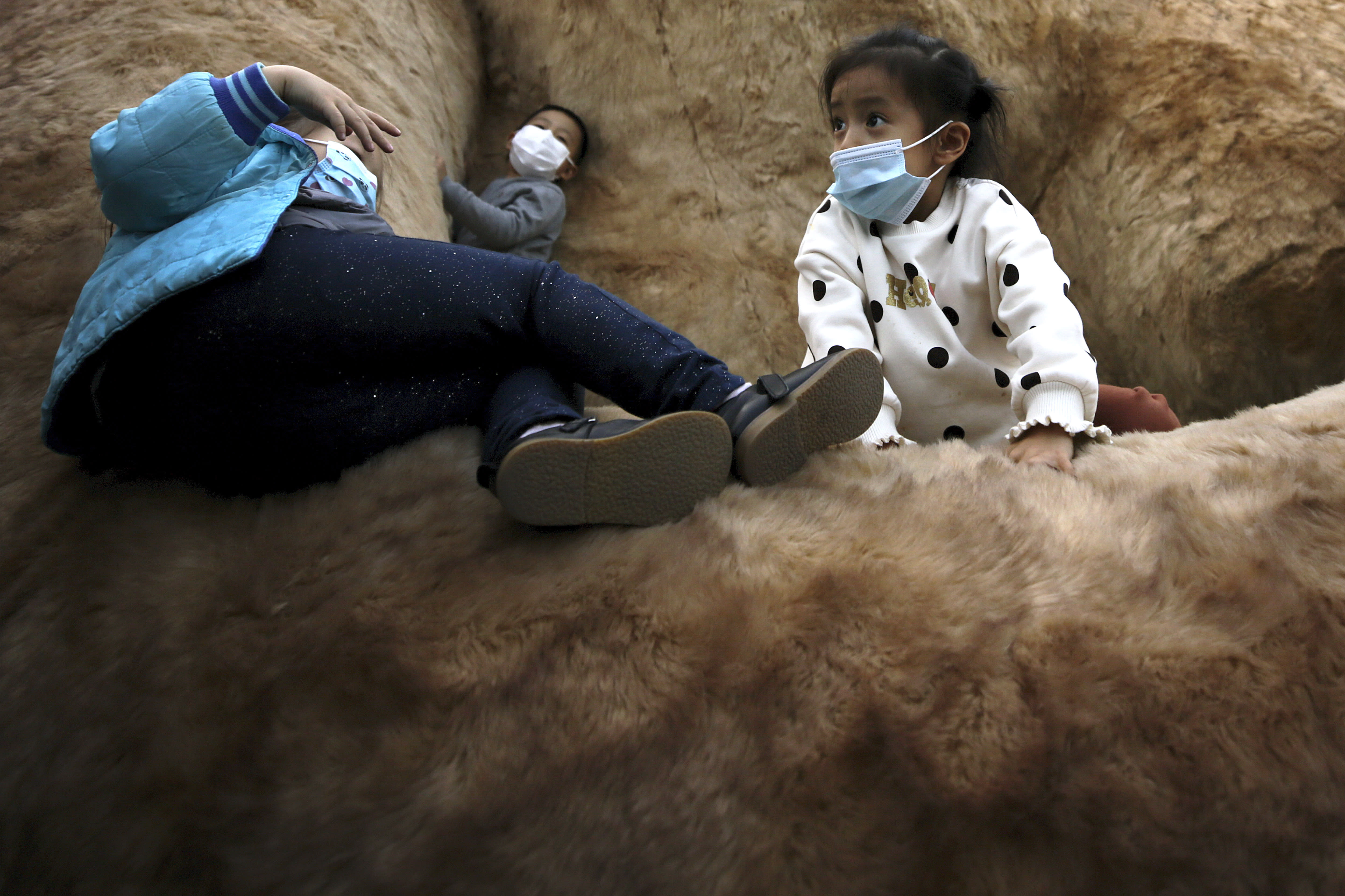 Children wearing face masks to help curb the spread of the coronavirus play on a giant cat structure on display at a commercial office building in Beijing, Sunday, Oct. 18, 2020. (AP Photo/Andy Wong)