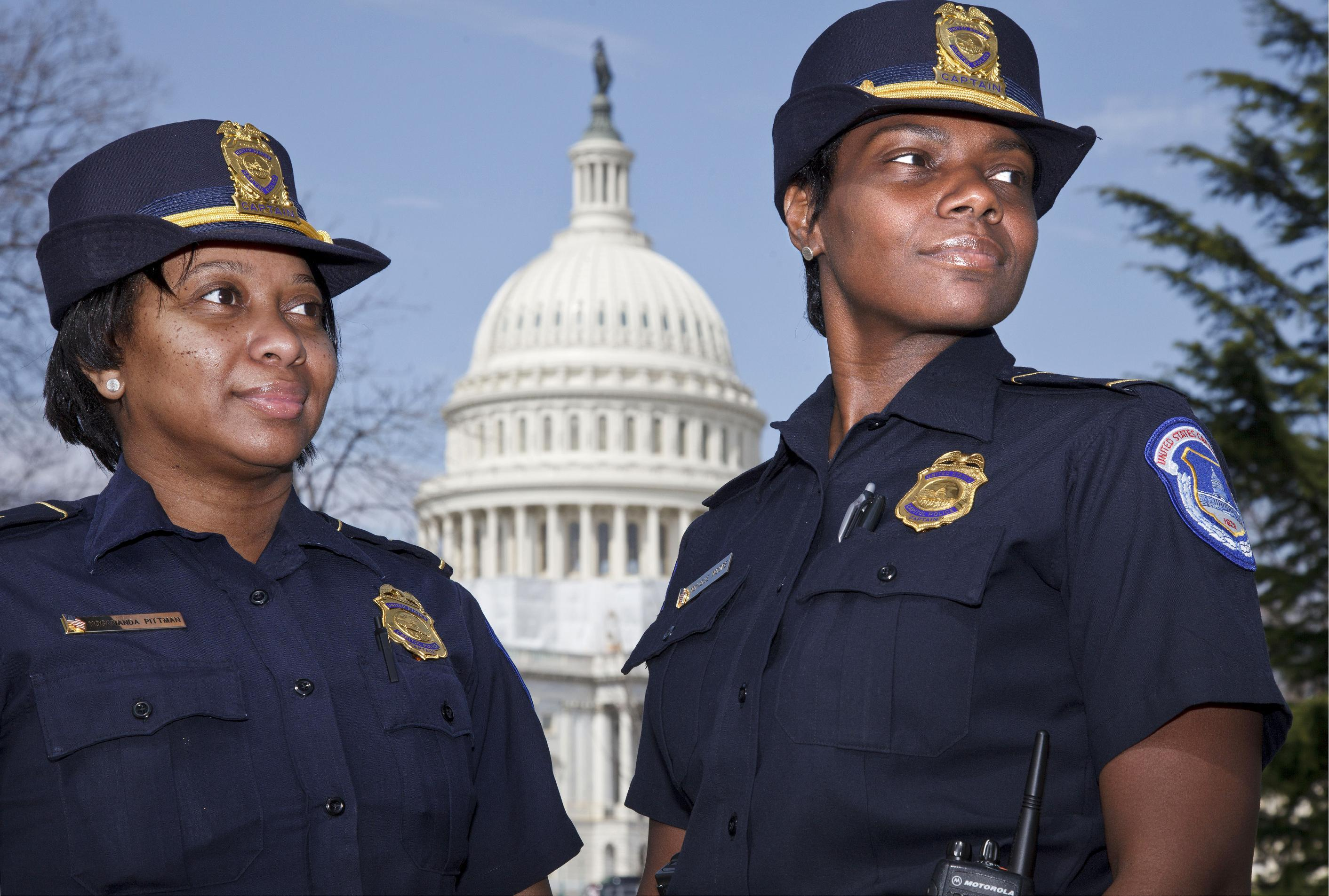 """Officers Yogananda """"Yogi"""" Pittman, left, and Monique Moore, right, the first two African-American women to be promoted to the rank of captain on the U.S. Capitol Police force, stand together on the East Lawn of the Capitol in Washington, Monday, March 19, 2012. (AP Photo/J. Scott Applewhite)"""