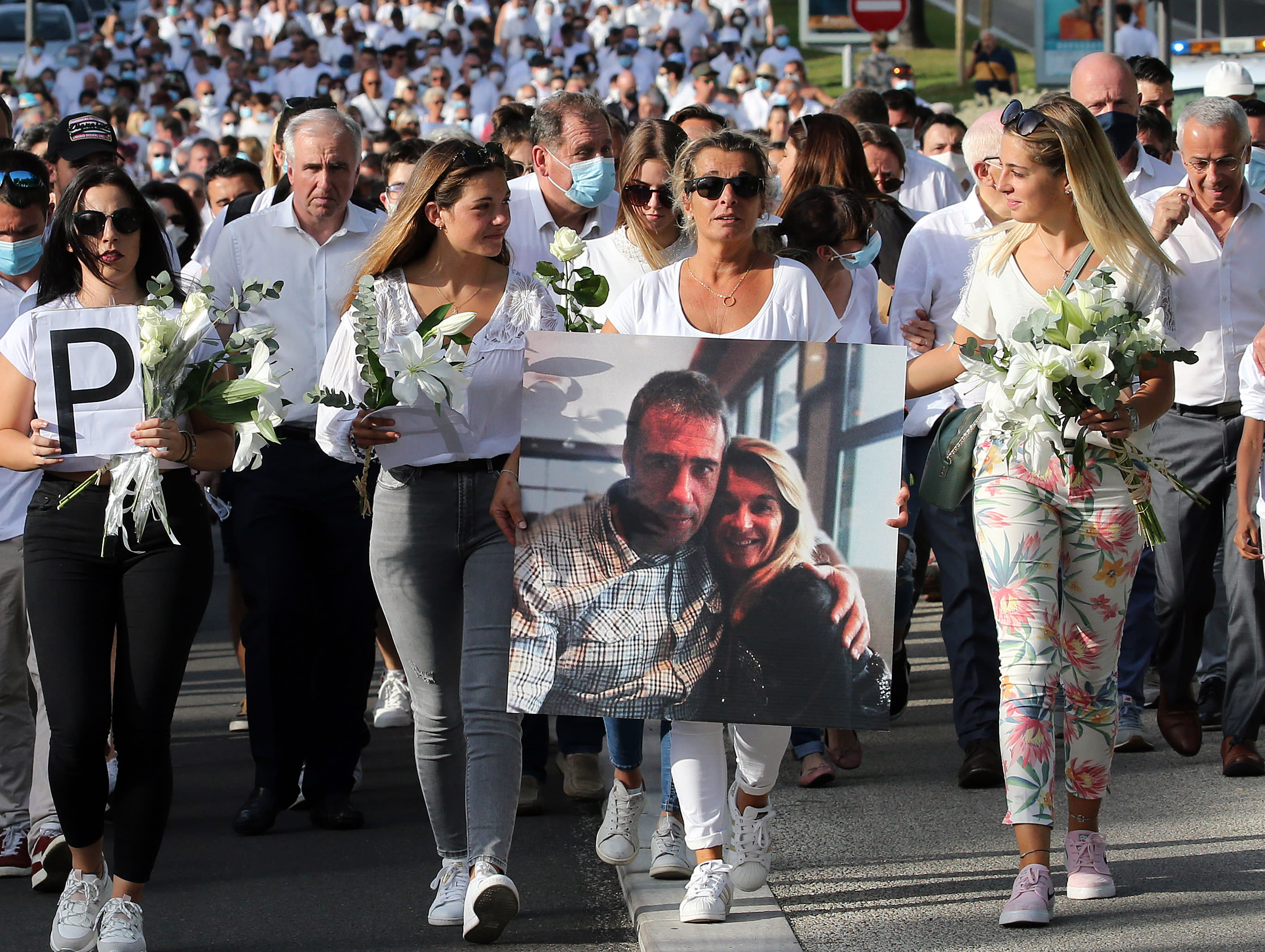 """This July 8, 2020 file photo shows Veronique Monguillot, wife of Philippe Monguillot, a bus driver who was attacked in Bayonne on Sunday night, holding a photo of her with her husband, during a protest march in Bayonne, southwestern France. The wife of a French bus driver savagely beaten after he asked four of his passengers to wear face masks aboard his vehicle called Saturday for """"exemplary punishment"""" after he died of his injuries. (AP Photo/Bob Edme)"""