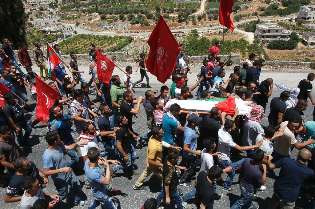 Palestinian mourners wave the party flag of the Popular Front of the Liberation of Palestine as they carry the body of Aref Jaradat, a 22-year old Palestinian who was injured during clashes with Israeli security forces in May 2016
