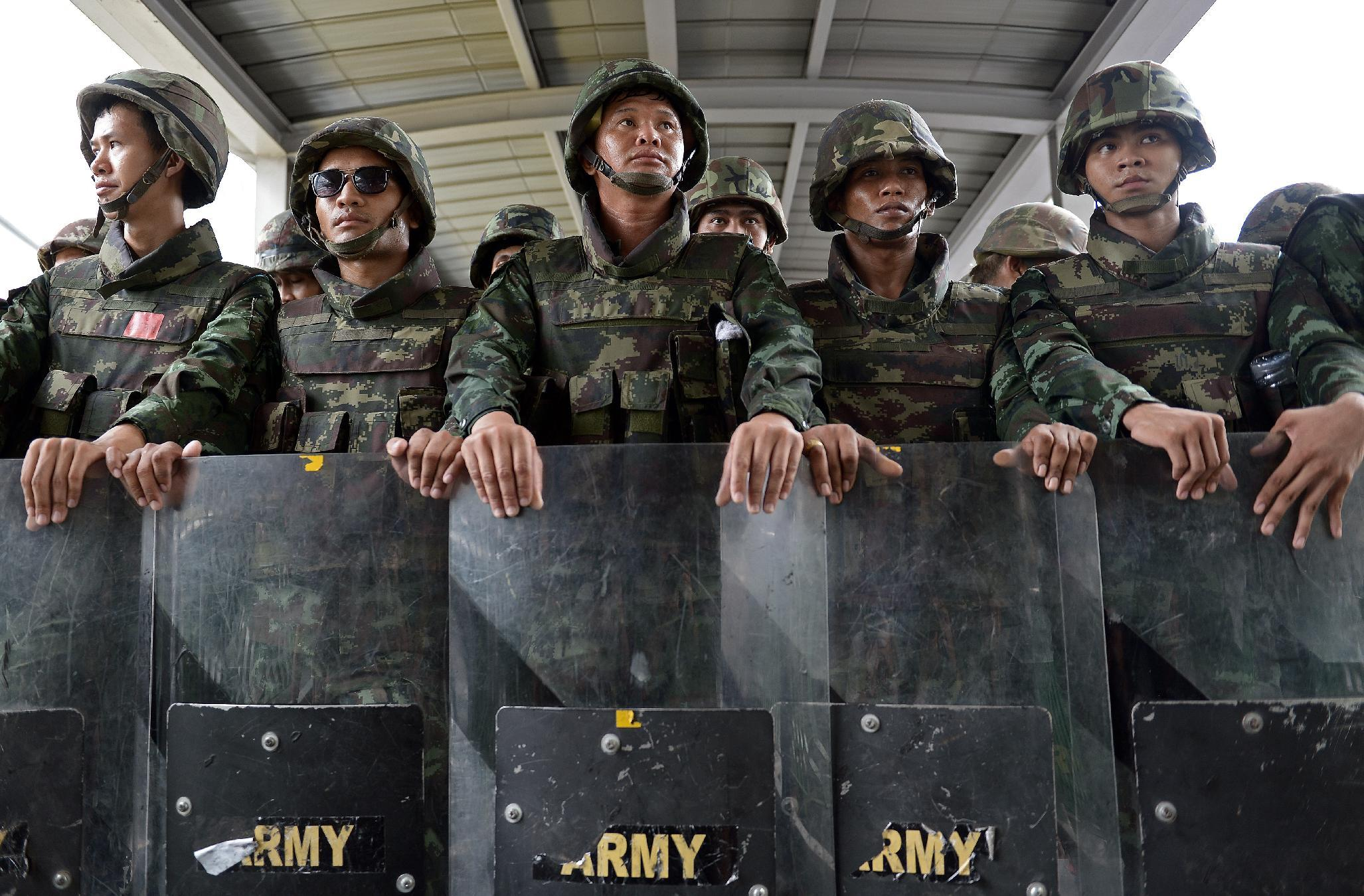 File photo shows Thai soldiers standing behind their shields after they sealed off an elevated train station leading to a shopping mall and broke up an anti-coup protest in downtown Bangkok on June 1, 2014