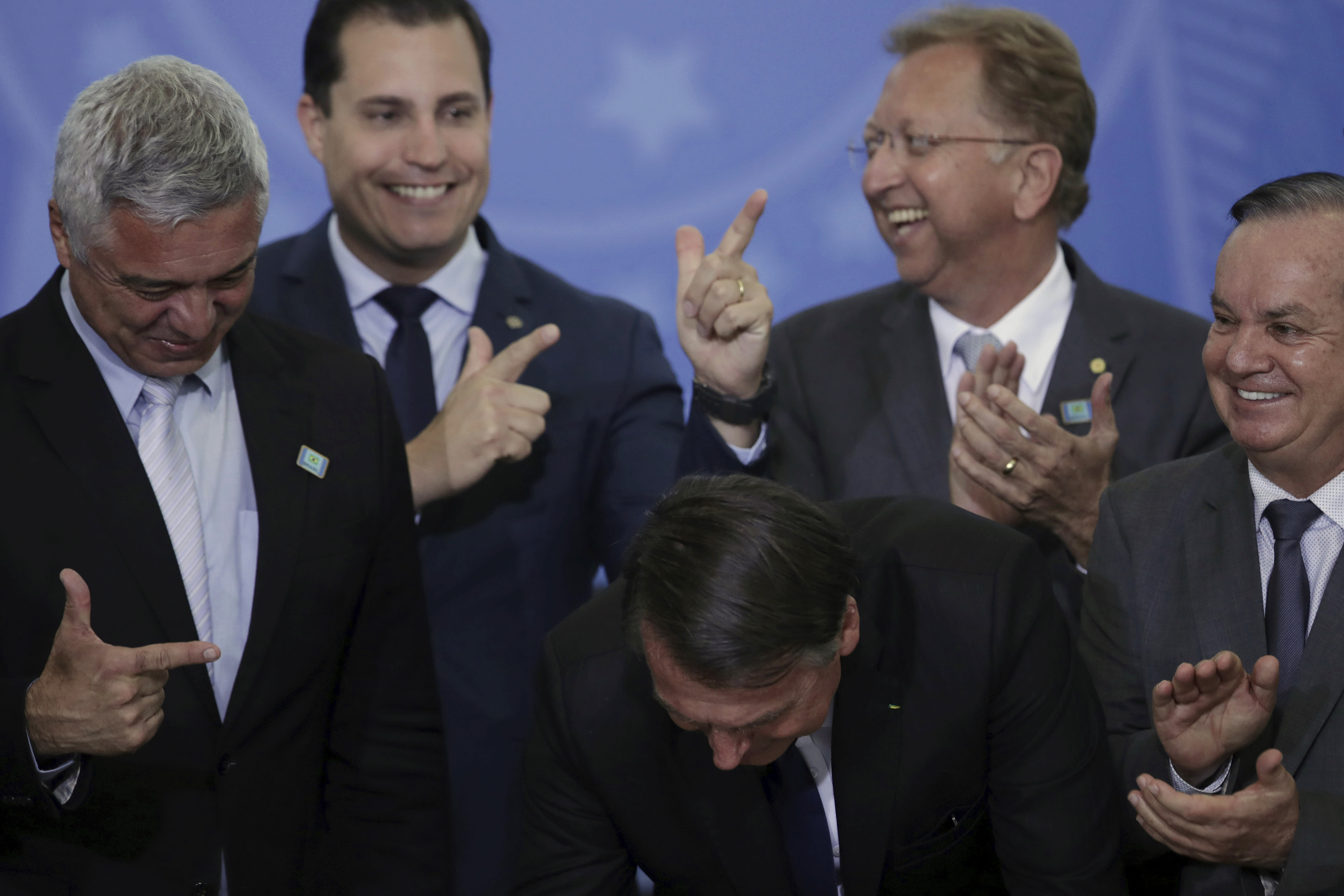 Lawmakers make finger-gun hand gestures as Brazil's President Jair Bolsonaro signs a second decree that eases gun restrictions, at Planalto presidential palace in Brasilia, Brazil, Tuesday, May 7, 2019. The decree opens Brazil's market to guns and ammunition made outside of Brazil according to a summary of the decree. Gun owners can now buy between 1,000 -5,000 rounds of ammunition per year depending on their license, up from 50 rounds. Lower-ranking military members can now carry guns after 10 years of service. (AP Photo/Eraldo Peres)