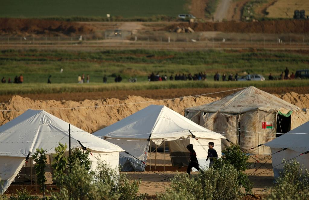 Children run past protest tents pitched by Palestinians on Gaza's border with Israel, visible in the background, on March 29, 2018 (AFP Photo/MAHMUD HAMS)