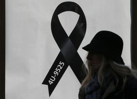 A woman walks past a black ribbon commemorating the 150 victims of Germanwings flight 4U 9525 outside Cologne's Cathedral