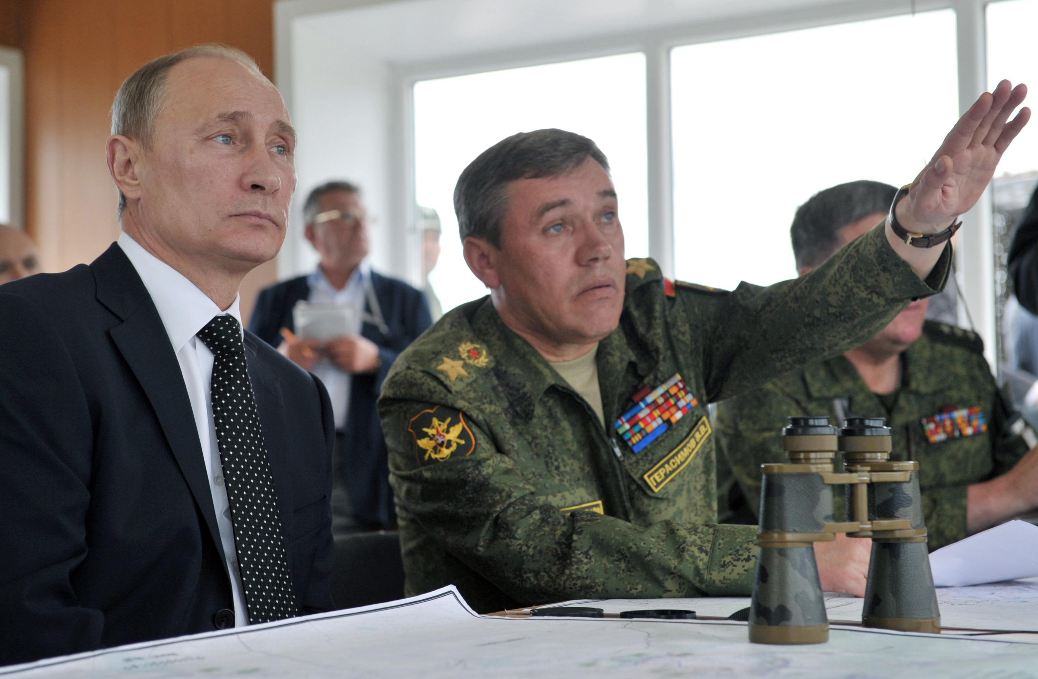 Russian President Vladimir Putin, left, listens to Chief of Russia's military's General Staff Valery Gerasimov, right, as he observes military exercises near the Baikal Lake in Russia on Wednesday, July 17, 2013. Russia has launched its biggest military maneuvers since Soviet times, involving 160,000 troops and about 5,000 tanks across Siberia and the far eastern region. (AP Photo/RIA Novosti, Alexei Nikolsky, Presidential Press Service)
