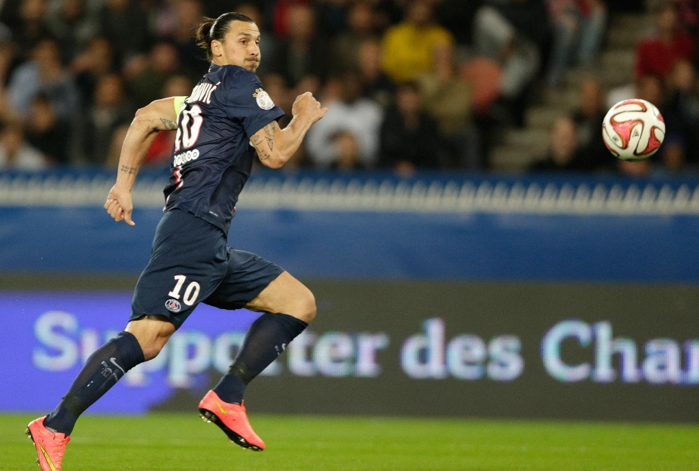 Paris Saint-Germain's Swedish midfielder Zlatan Ibrahimovic eyes the ball during a French L1 match against Lyon at the Parc des Princes stadium in Paris on September 21, 2014