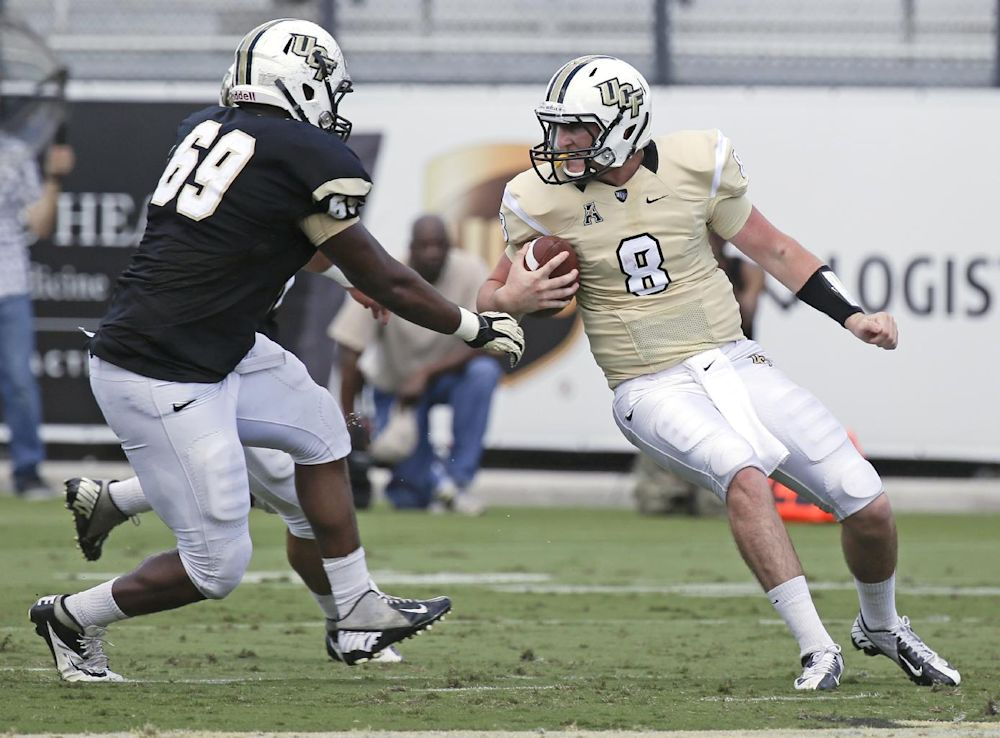 Central Florida quarterback Tyler Harris (8) tries to scramble before he is sacked by defensive lineman Thomas Niles (69) during the spring NCAA college football game in Orlando, Fla., Saturday, April 12, 2014