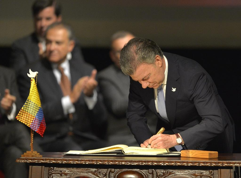 Colombian President Juan Manuel Santos signs the historic peace agreement between the Colombian government and the Revolutionary Armed Forces of Colombia in Bogota, on November 24, 2016 (AFP Photo/Luis Robayo)