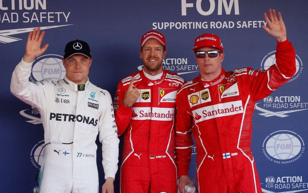 Sebastian Vettel (centre) celebrates his pole position in Russia with Valtteri Bottas (left) and Kimi Raikkonen (right) - REUTERS