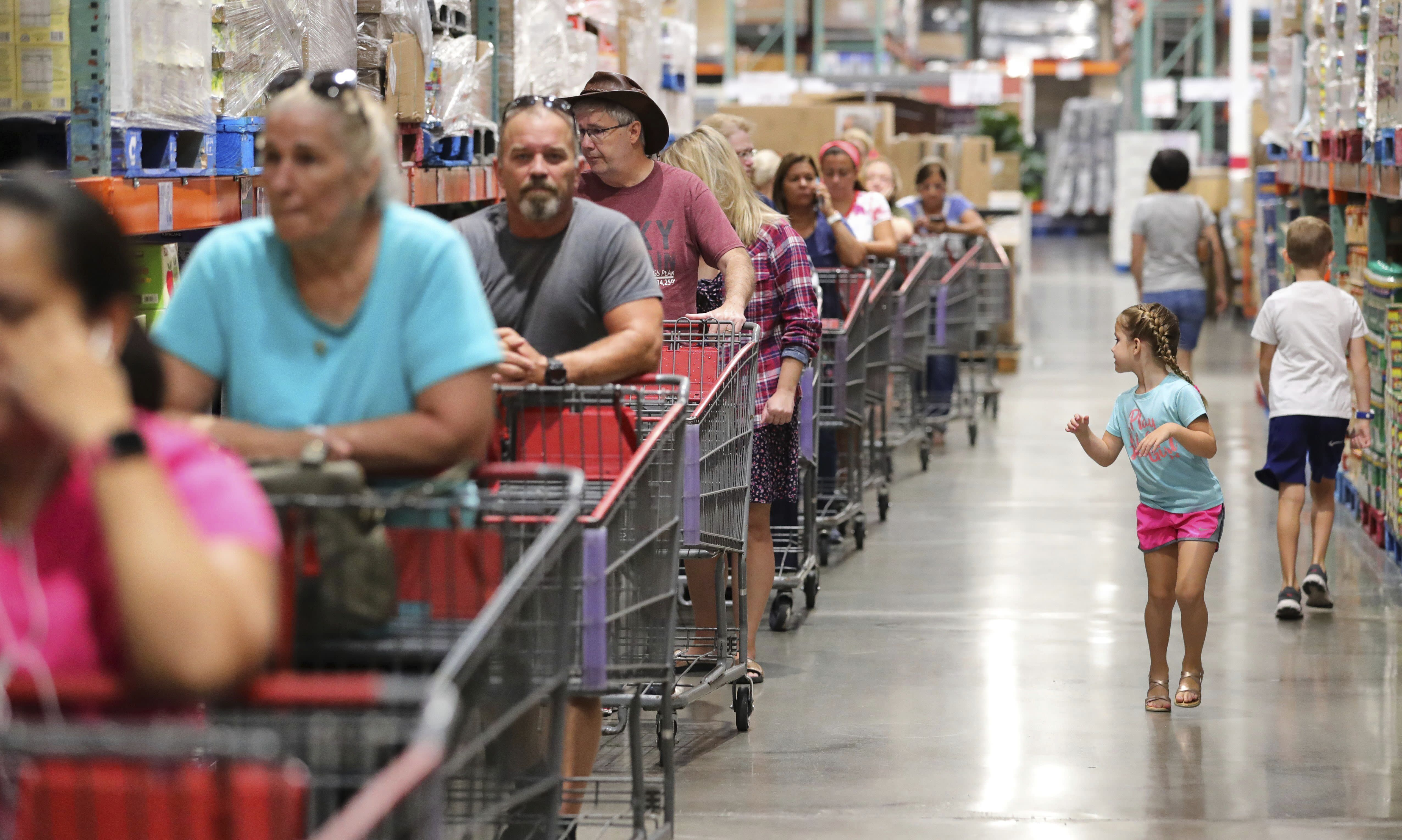 FILE - In this Aug. 30, 2019, file photo shoppers wait in line to get two cases of bottled water at the Costco store in Altamonte Springs, Fla. On Friday, Sept. 13, the Commerce Department releases U.S. retail sales data for August. (Joe Burbank/Orlando Sentinel via AP, File)