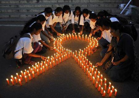 Staff members of a government-run pharmaceutical college light candles arranged in the formation of a ribbon to promote cancer awareness and mark World Cancer Day, in the southern Indian city of Bengaluru, formerly known as Bangalore