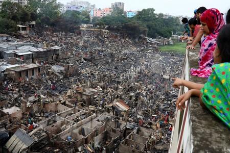People look on to the slum that burnt out in Dhaka