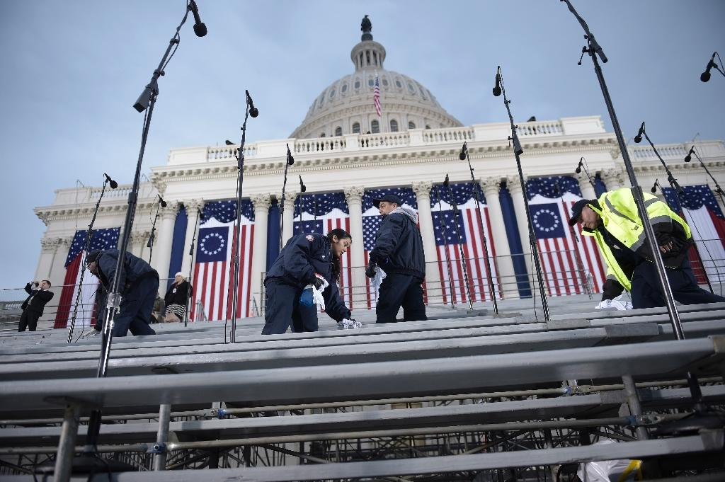 Workers prepare spectators' seats below the dome of the US Capitol in Washington, DC on January 20, 2017, before the swearing-in ceremony for US President-elect Donald Trump (AFP Photo/Brendan SMIALOWSKI)