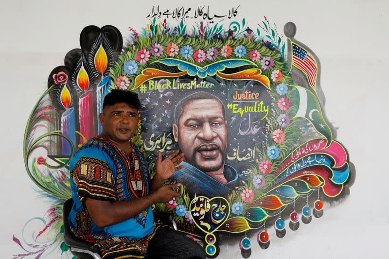 FILE PHOTO: FILE PHOTO: Pakistani truck-art painter Haider Ali, 40, gestures as he speaks with Reuters next to a mural he painted, depicting George Floyd, who died in Minneapolis police custody in U.S., in Karachi