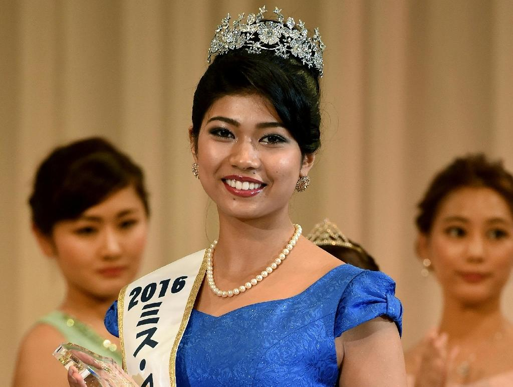 Priyanka Yoshikawa smiles as she holds the trophy after winning the Miss Japan title at the Miss World Japan 2016 Beauty Pageant in Tokyo on September 5, 2016