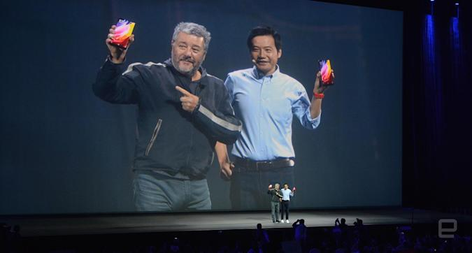 """French designer Philippe Starck and Xiaomi CEO Lei Jun holding their Mi MIX """"concept phones"""" on the stage in Beijing."""