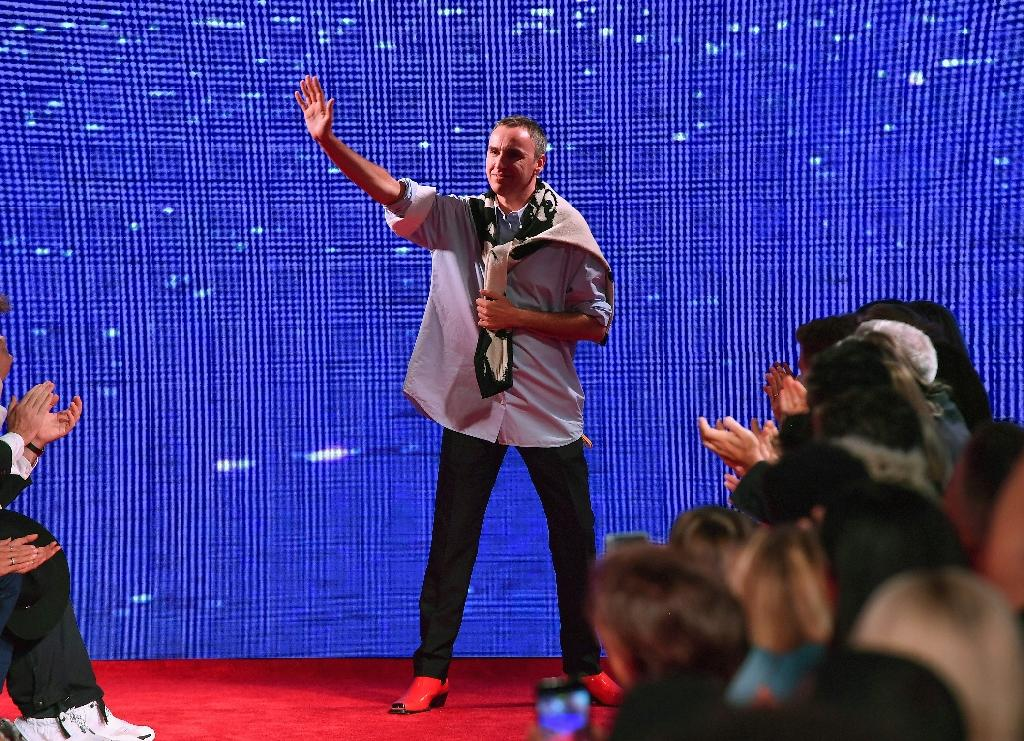 Belgian fashion designer Raf Simons waves to his guests, on the runway during New York Fashion Week in September 2018