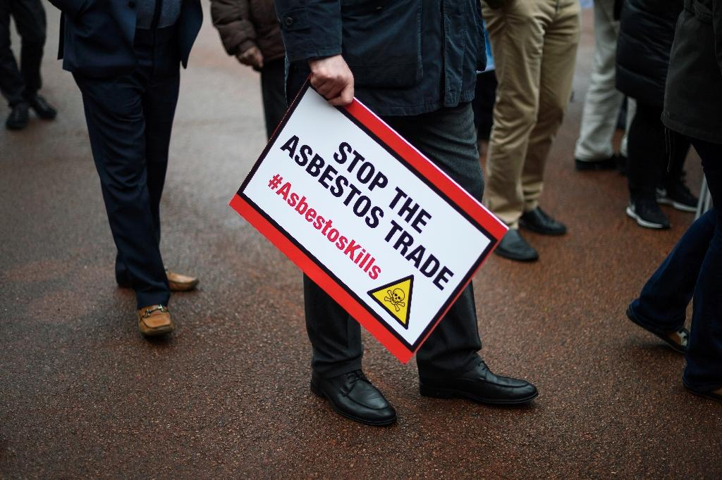 A unionist holds a placard after a demonstration to demand that white asbestos be included on the list of hazardous material of the UN Rotterdam Convention, on April 28, 2017 in Geneva
