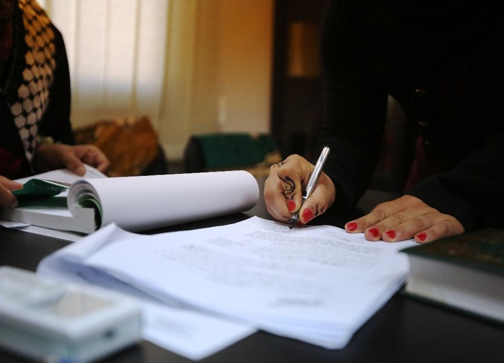 Rawan (right) signs an official document after Tahrir Hamad (left) her and her husband Thaer man and wife (AFP Photo/Abbas Momani)
