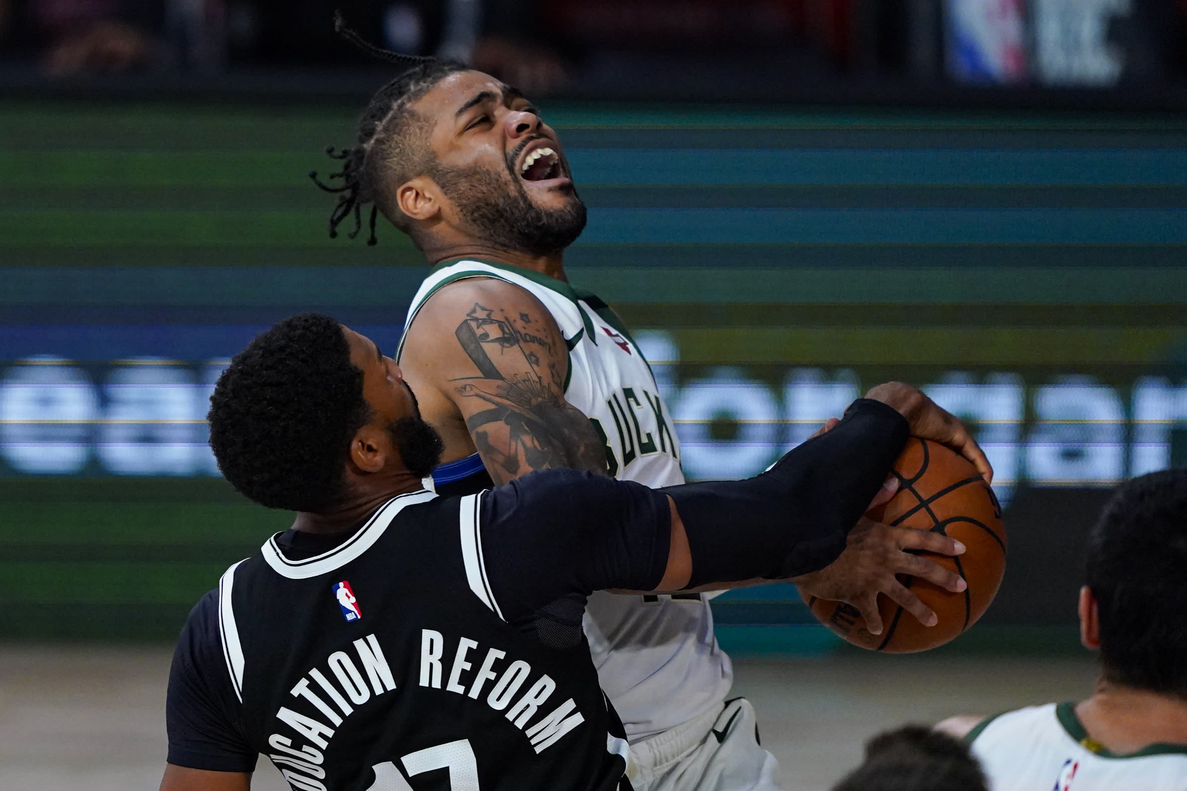 Milwaukee Bucks guard Frank Mason III (15) is fouled as he shoots by Brooklyn Nets guard Garrett Temple (17) during the second half of an NBA basketball game Tuesday, Aug. 4, 2020 in Lake Buena Vista, Fla. (AP Photo/Ashley Landis)