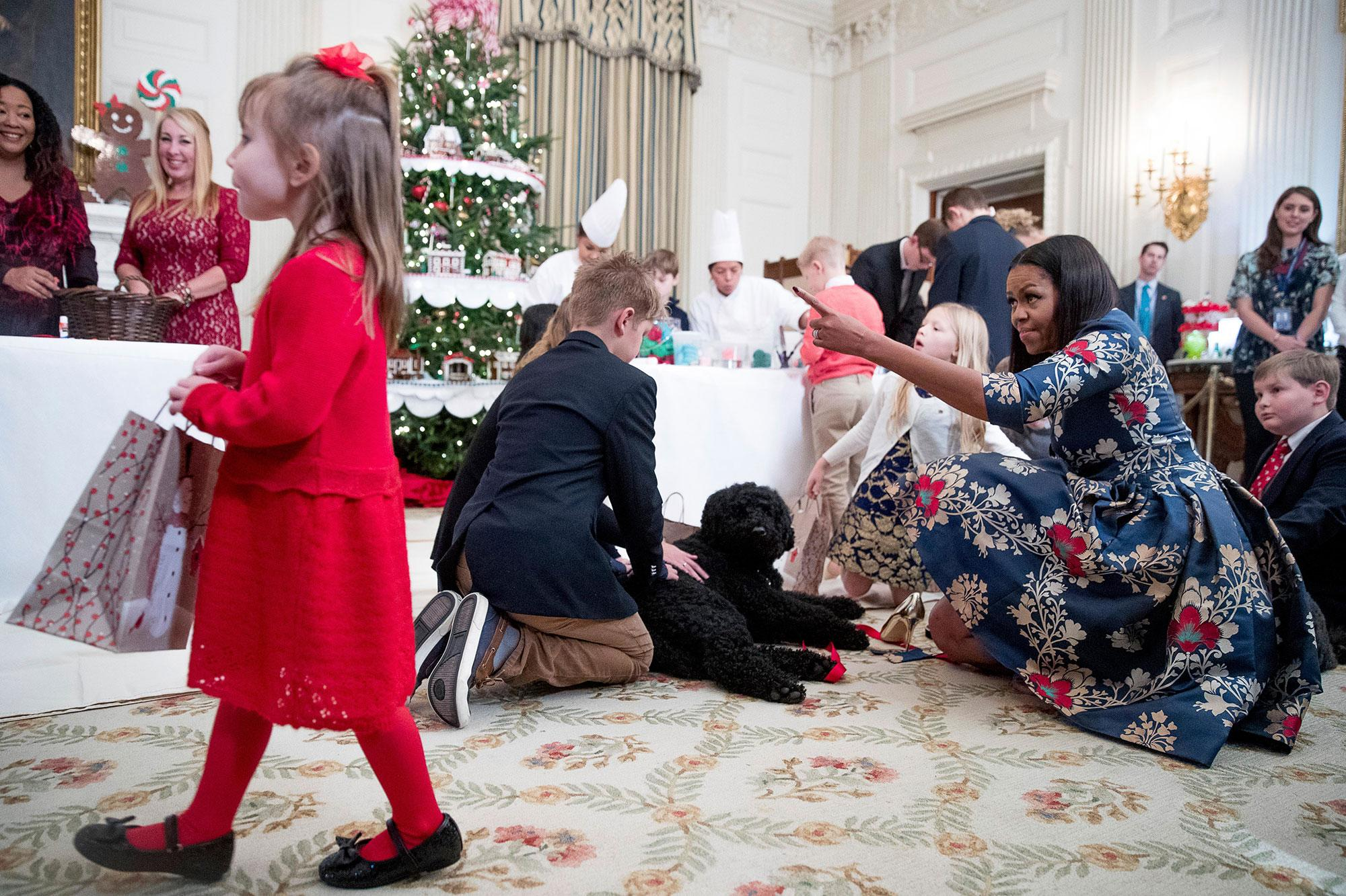 <p>First lady Michelle Obama brings in the first family's dogs Sunny and Bo, as children of military families make holiday crafts and treats in the State Dining Room of the White House in Washington, Tuesday, Nov. 29, 2016, during a preview of the 2016 holiday decor for military families. (Photo: Andrew Harnik/AP) </p>