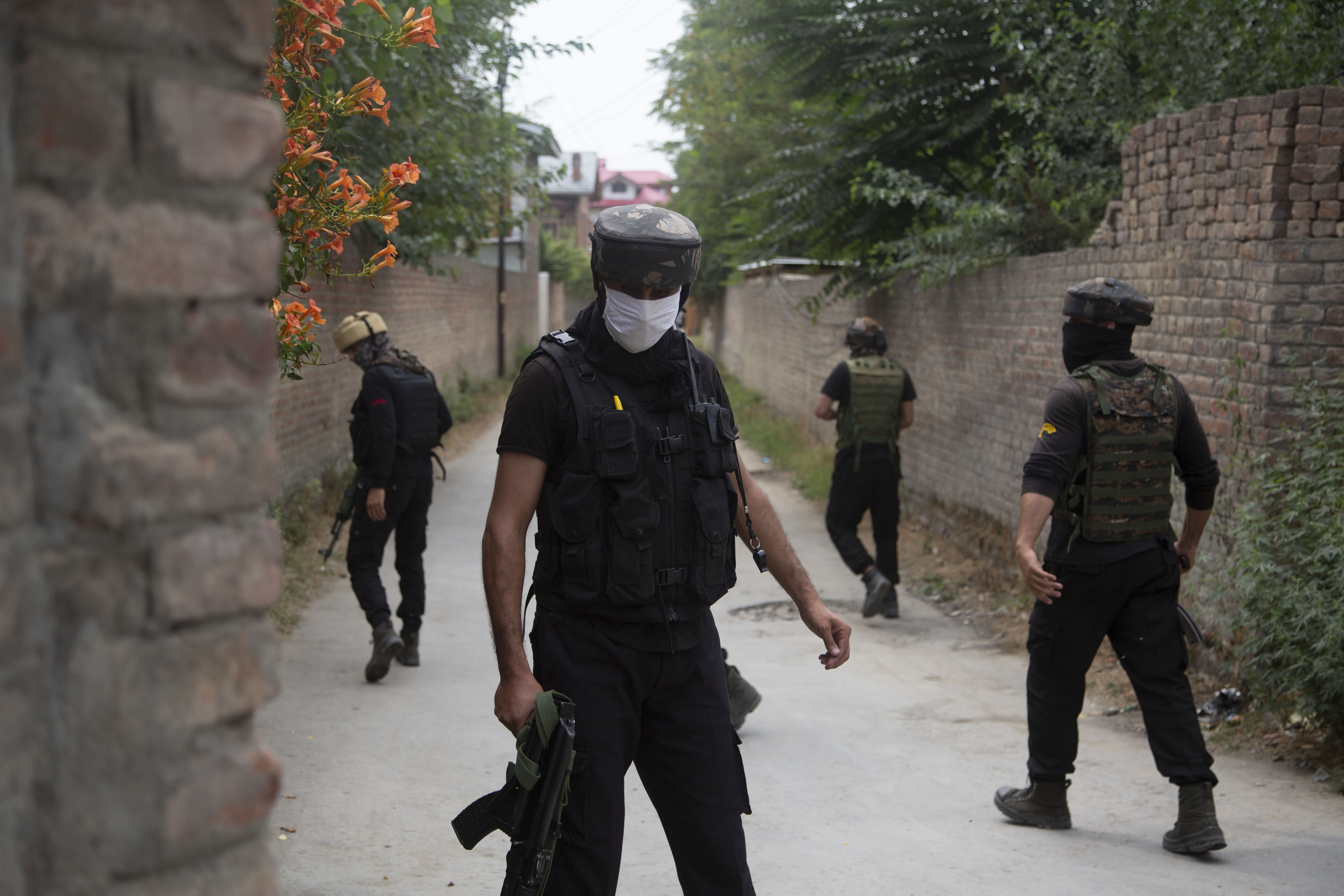 Members of special Operations Group (SOG) of Jammu and Kashmir police examine at the site of an attack on policemen on the outskirts of Srinagar, Indian controlled Kashmir, Friday, Aug. 14, 2020. Anti-India rebels in Indian-controlled Kashmir Friday attacked a police party in the disputed region's main city, killing two police officials and injuring another, police said. (AP Photo/Mukhtar Khan)