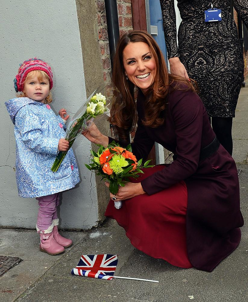 Kate bends down to receive flowers from an adorable two-year-old, looking lovely in Alexander McQueen.