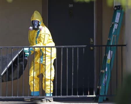 A worker wearing a hazardous material suit arrives at the apartment unit where a man diagnosed with the Ebola virus was staying in Dallas
