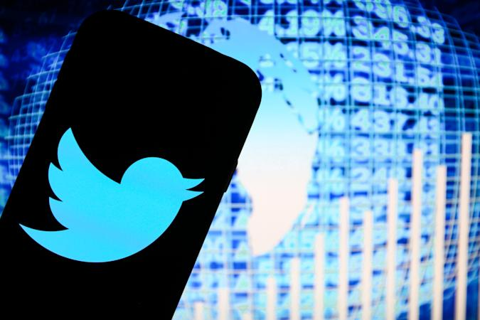 POLAND - 2020/11/20: In this photo illustration a Twitter social media app logo seen displayed on a smartphone with blue world data stats in the background. (Photo Illustration by Filip Radwanski/SOPA Images/LightRocket via Getty Images)