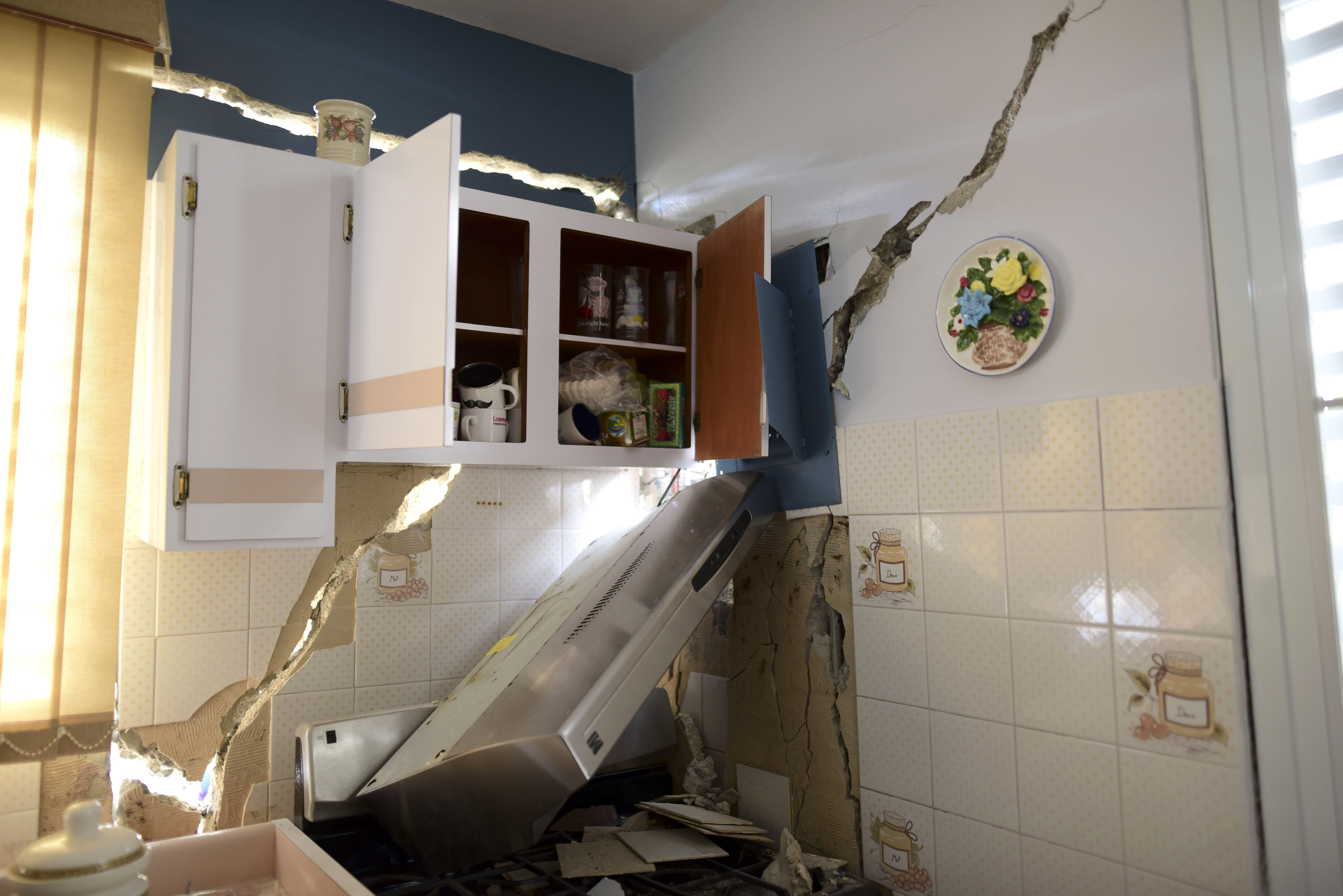 The house of William Mercuchi is damaged after the previous day's magnitude 6.4 earthquake in Yauco, Puerto Rico, Wednesday, Jan. 8, 2020. More than 250,000 Puerto Ricans remained without water on Wednesday and another half a million without power, which also affected telecommunications. (AP Photo/Carlos Giusti)