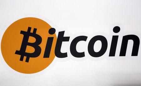 FILE PHOTO - A Bitcoin logo is displayed at the Bitcoin Center New York City in New York's financial district in NY, U.S. on July 28, 2015. REUTERS/Brendan McDermid/File Photo