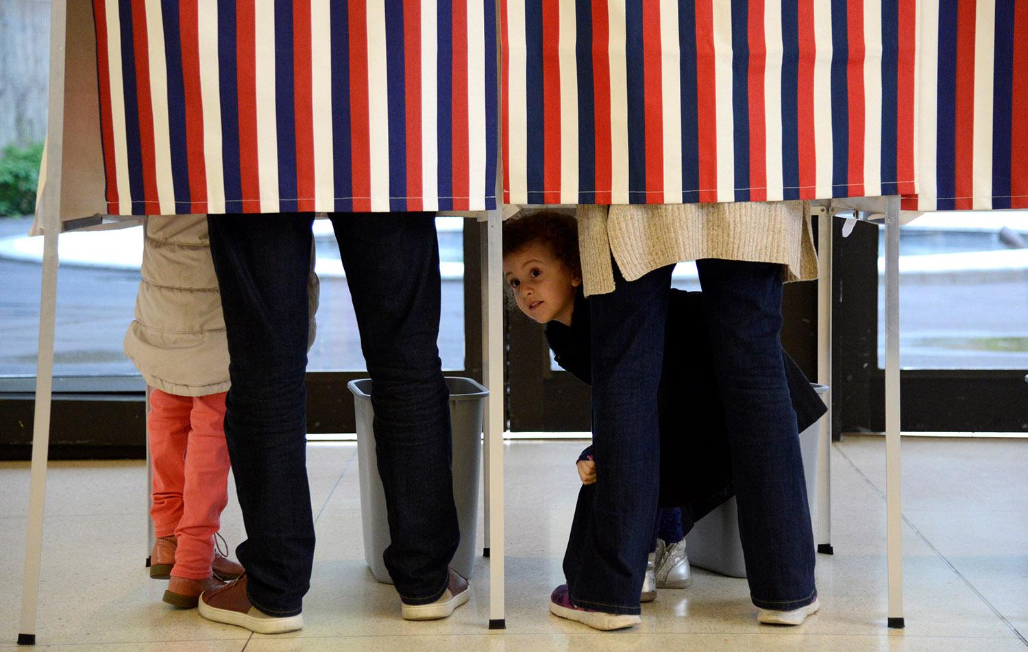 <p>A child looks out from a voting booth as French citizens living in the United States cast their ballots for the French presidential run-off between Emmanuel Macron and Marine Le Pen, at the French Embassy in Washington, May 6, 2017. (Photo: Mike Theiler/Reuters) </p>