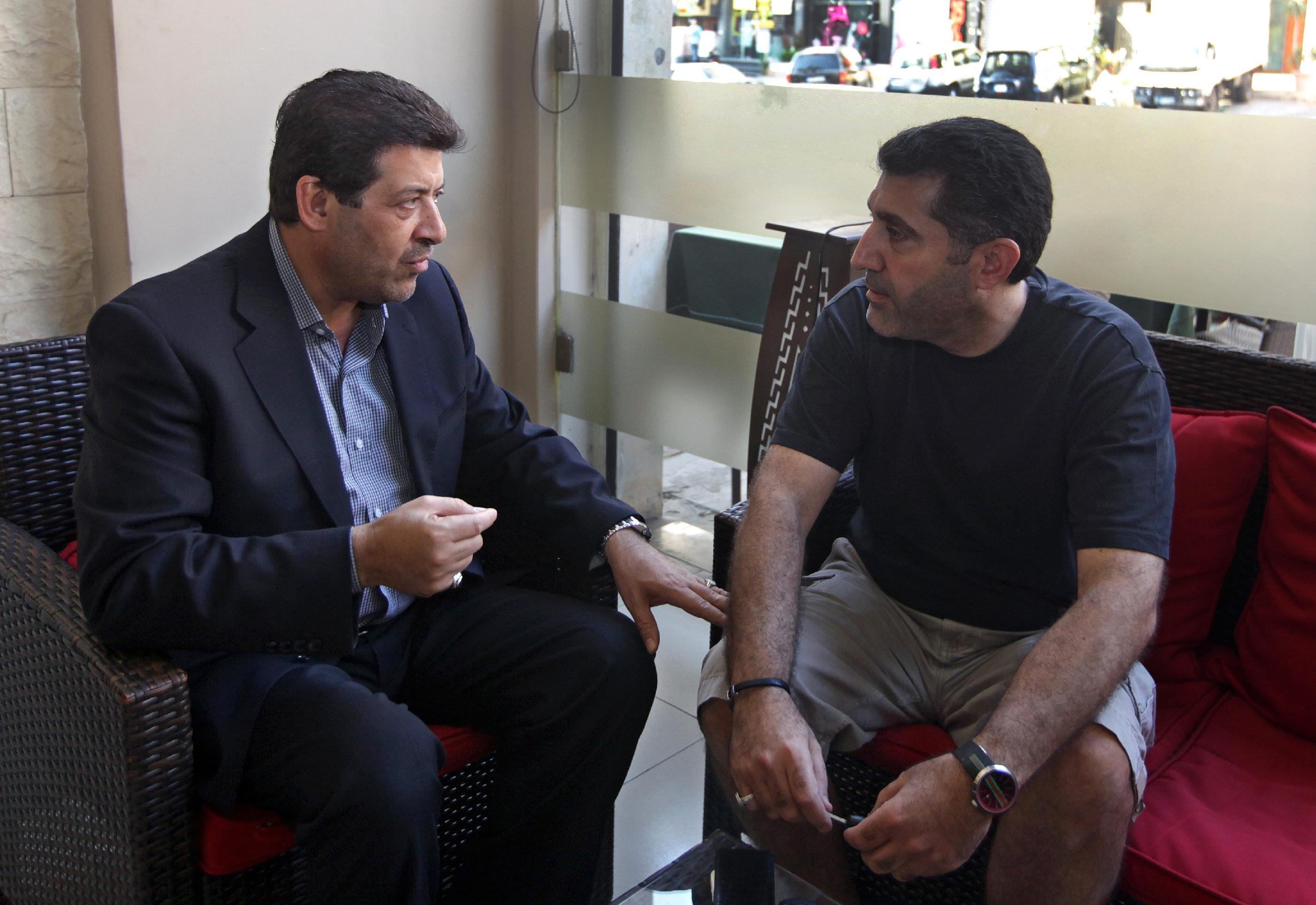 In this Wednesday, July 10, 2013 photo, Shiites Hassan Alayan, left, who was expelled from the UAE in 2009, speaks with Ali Rashid, right, who was expelled from the UAE in 2011, at a cafe in Beirut, Lebanon. Long considered by authorities as a security threat, hundreds of Shiites have been quietly expelled from the United Arab Emirates over the past few years on suspicion of being supporters of Hezbollah. Diplomats and Shiite families in Lebanon say deportations have surged in the past few months after the militant group group publicly joined the civil war in Syria on the side of President Bashar Assad, an arch enemy of the Gulf's rulers.(AP Photo/Bilal Hussein)