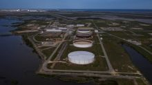 Oil hovers near 13-month highs as storm hits U.S. output, Fed assures rates staying low